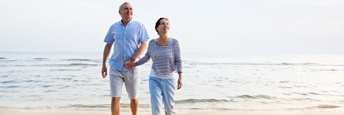 Image of man and woman walking on beach - stem cell treatments for osteoarthritis